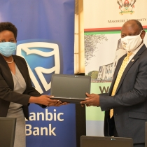 Stanbic Bank's Chief Executive, Anne Juuko hands over one of the donated Laptops to Makerere University's Vice-Chancellor Prof Barnabas Nawangwe