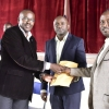 Maj Chris Magezi Handsover the cash envolope to St Mary's Kisubi Deputy Headmaster Justus Katatutmba