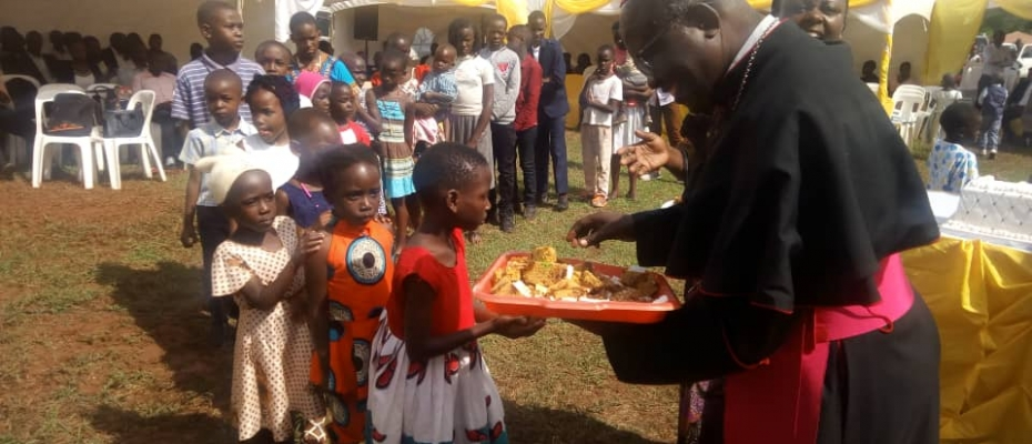 Bishop Vincent Kirabo serving cake with the children after the mass. Courtesy photo