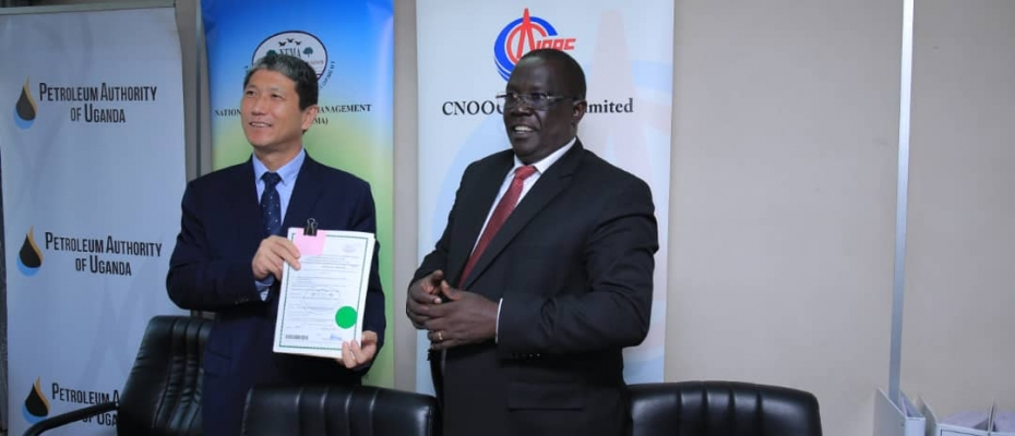 Zhao Shunqiang, the President, CNOOC Uganda Limited receives the certifcate from Tom Okurut (R), NEMA ED