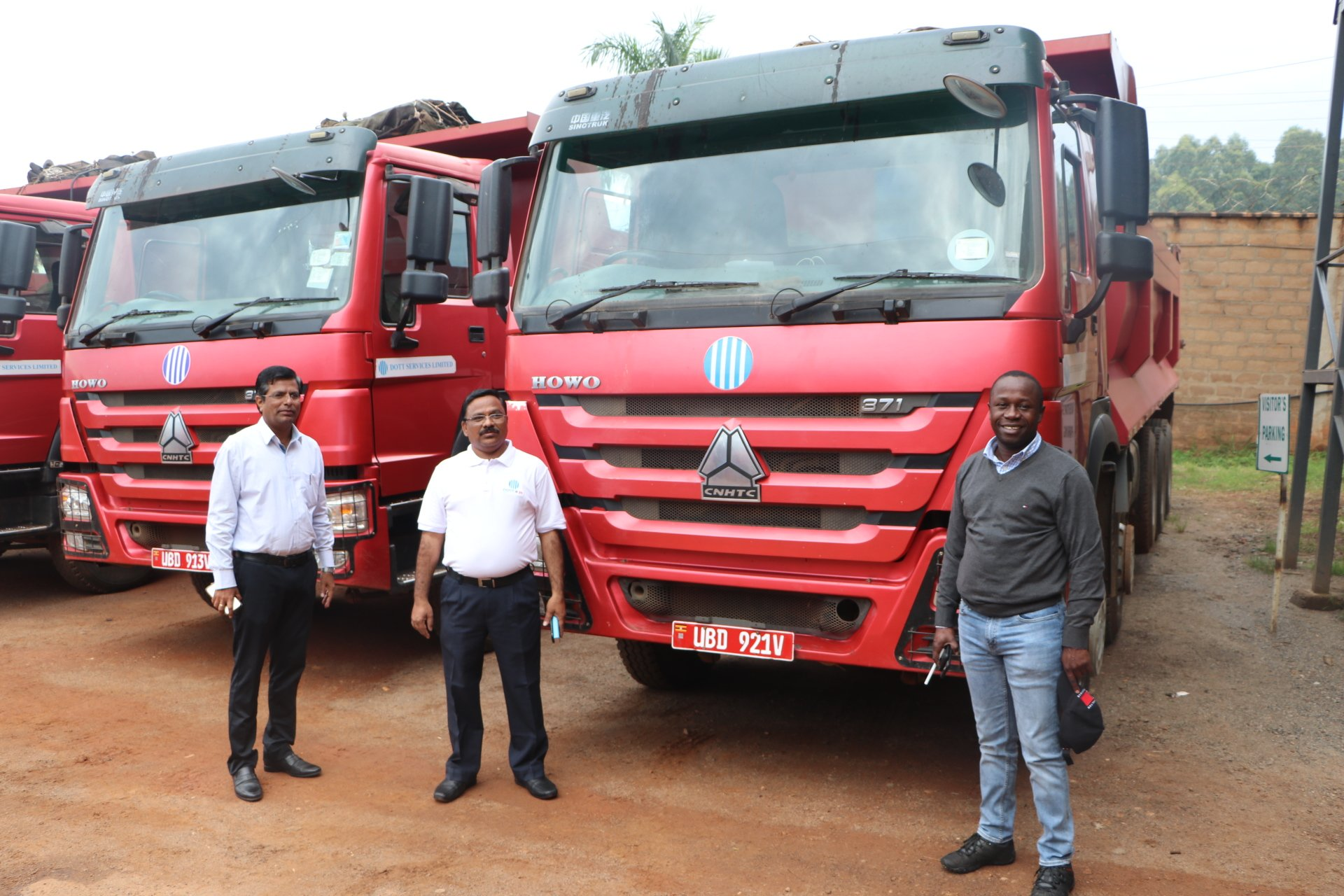 Minister Peter Ogwang (R) receiving 20 trucks from Dott Services Limited