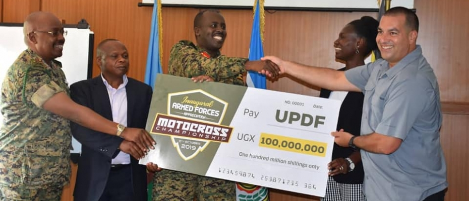 CDF Muhoozi (C) receives the Sh100M dummy cheque from UMC President Dusman Okee. DPU photo