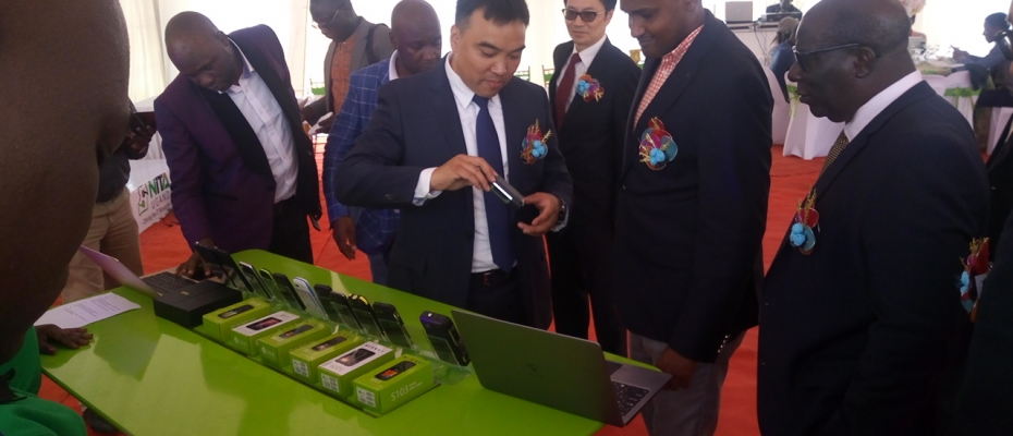 ICT minister Frank Tumwebaze inspects some of the locally manufactured phones by SIMI Mobile.