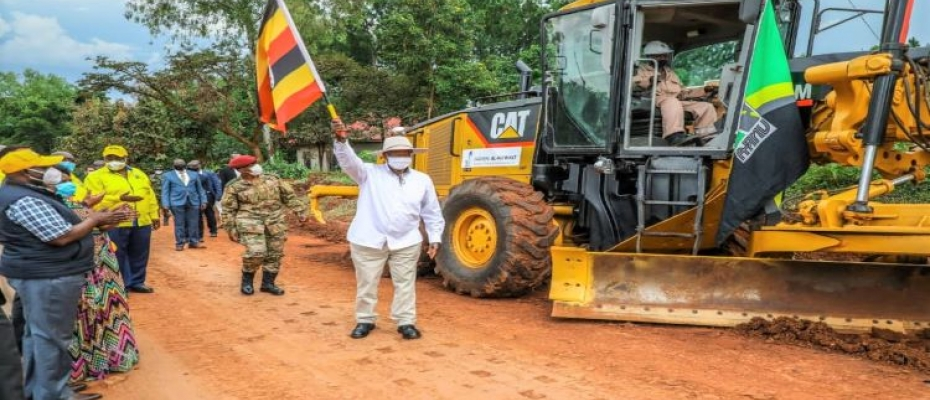 Deputy Speaker Oulanyah (L) and guests cheering on President Museveni as he flags off the mega road works in Lira district
